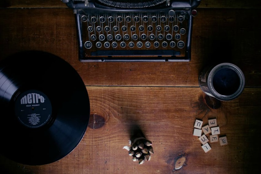 Image of a countertop with a typewriting machine coffee and a vinyl disk Photo by Unsplash