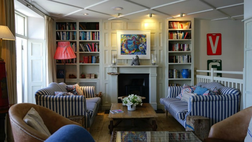 Image is of a living room with four chairs surrounding a table and a unique bookshelf against one wall Photo by Mike Bird