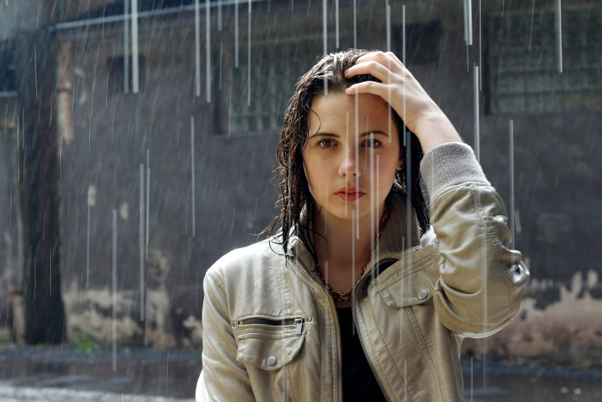 Woman standing in the rain and looking directly at the camera Photo by Unsplash