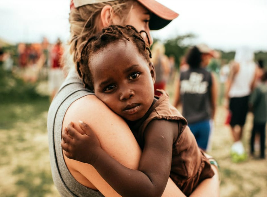 Image of a child being carried by someone The child looks worried Photo by Unsplash