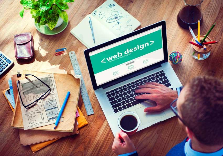 Man sitting at laptop that says web design