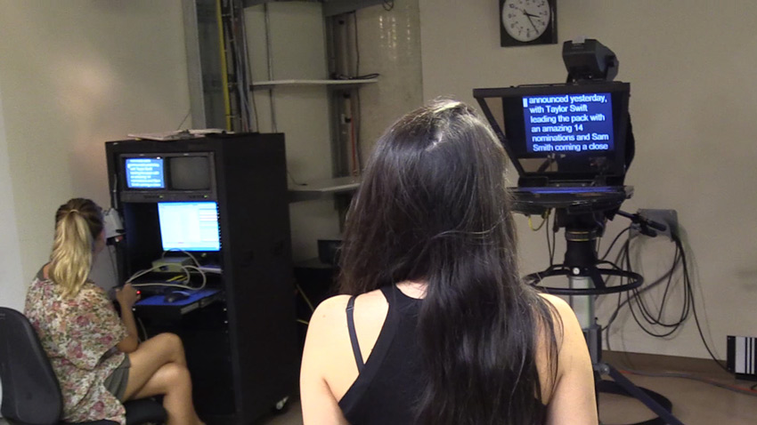 Woman reads from a teleprompter
